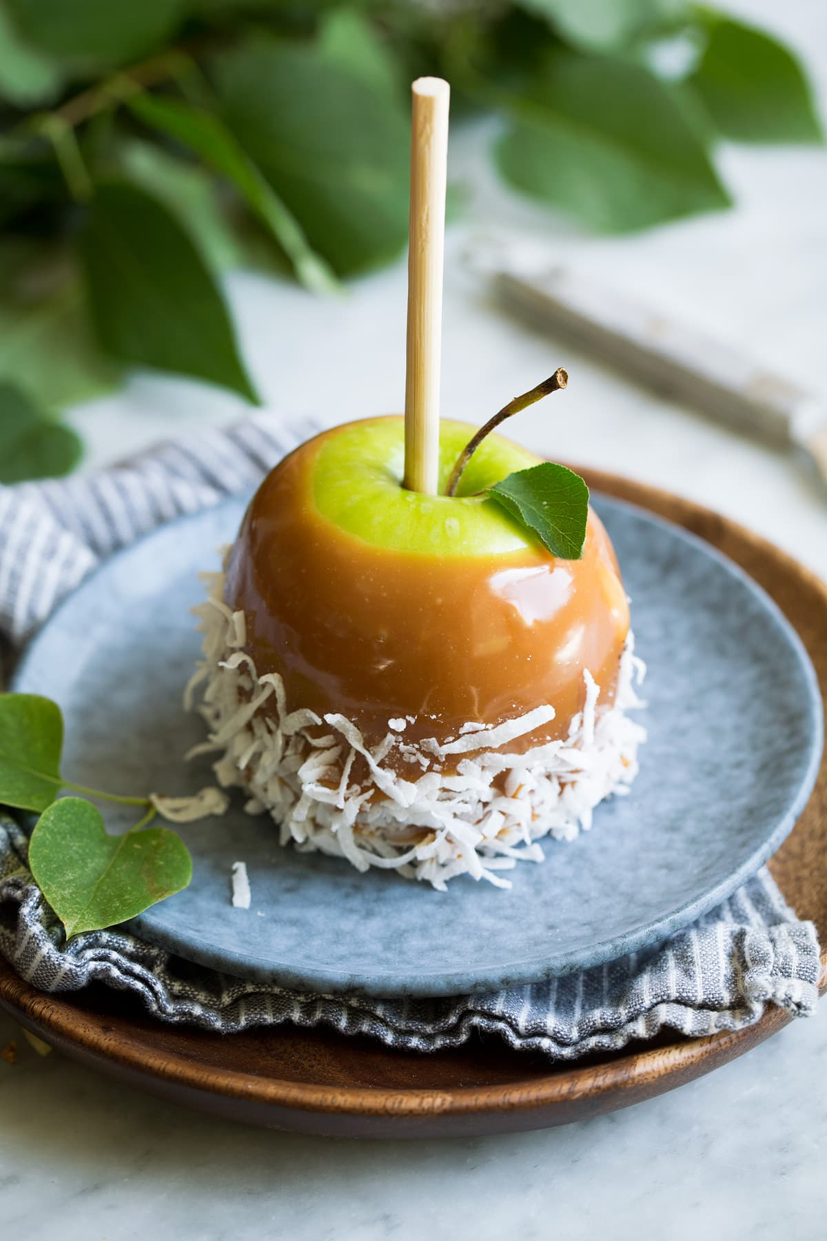 Single caramel apple rolled in shredded coconut sitting on a blue plate on top of a wooden plate.