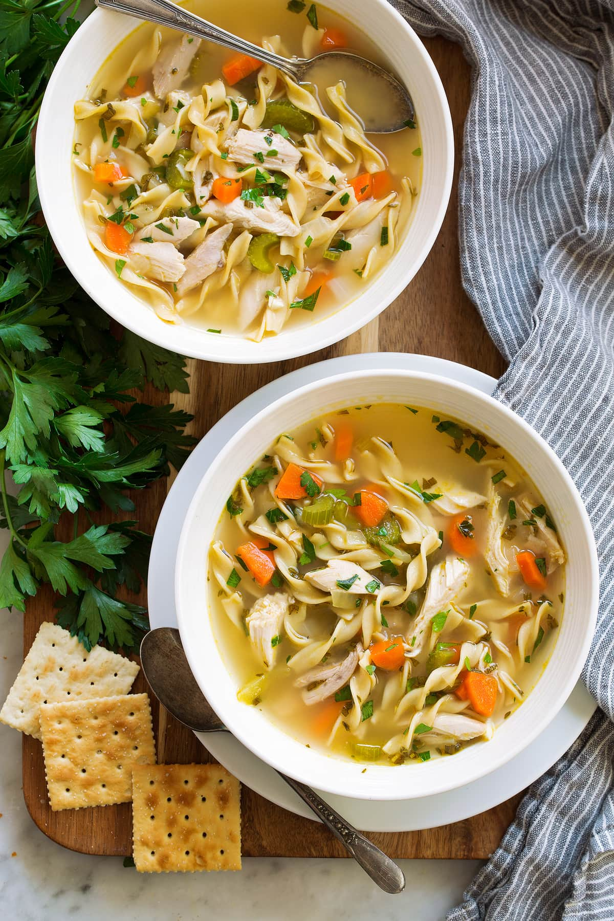 Two servings of the best chicken noodle soup in white bowls.