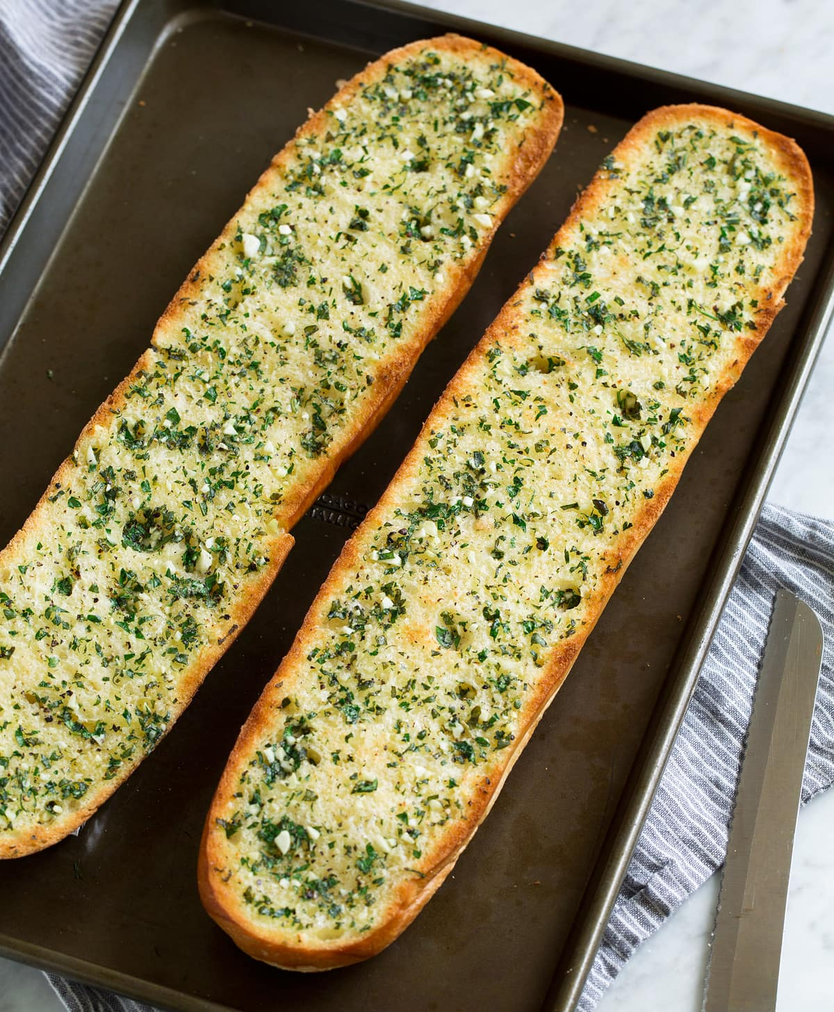 Two garlic bread halves on a dark baking sheet. Shown after toasting.
