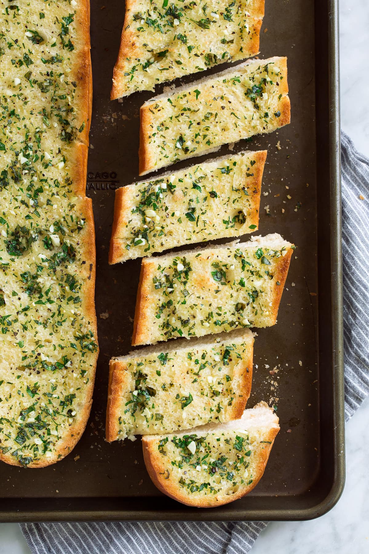 Loaf of garlic bread cut into slices on a baking sheet.