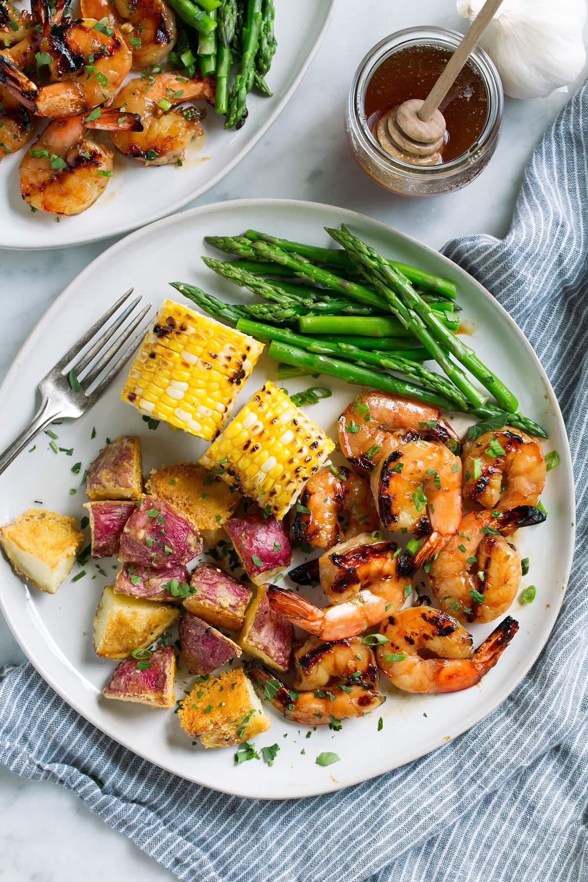 Grilled shrimp on a plate with a side of grilled corn, steamed asparagus and roasted potatoes.