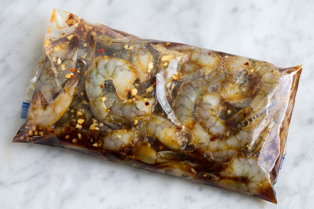 Shrimp in marinade in a plastic resealable bag.