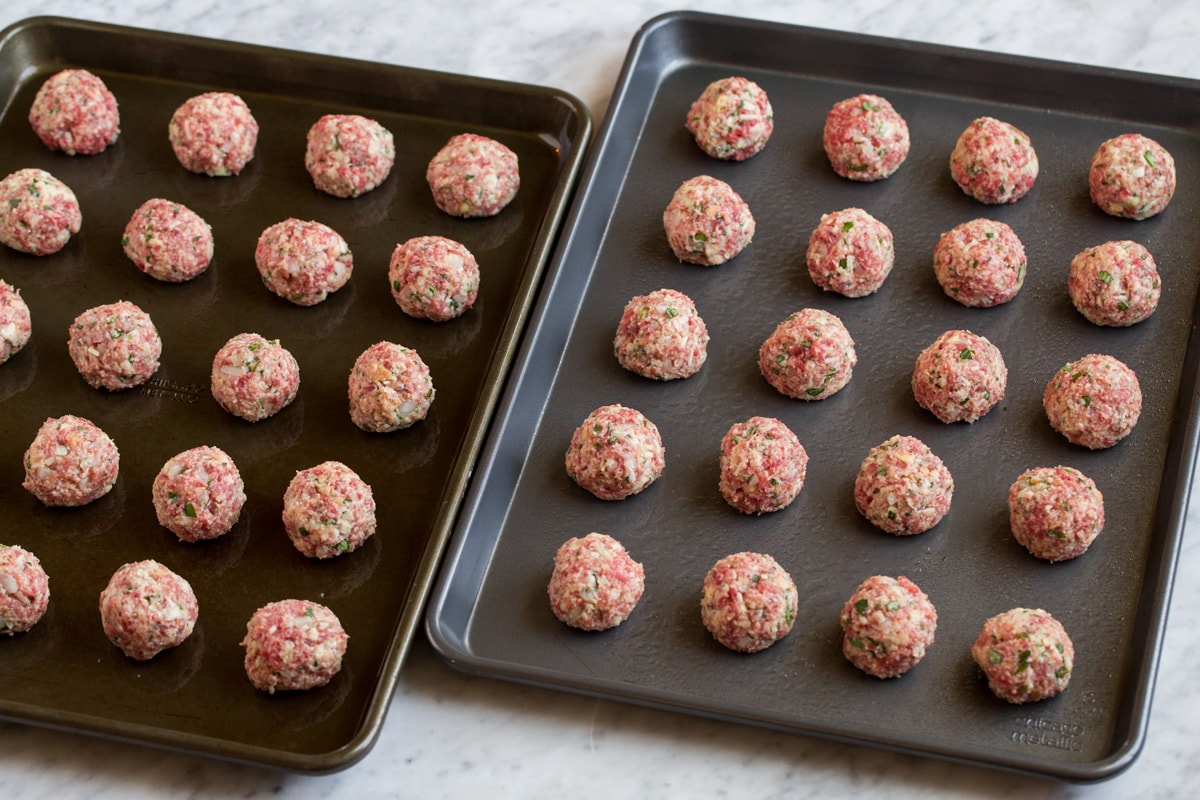 Raw meatballs on two baking sheets.