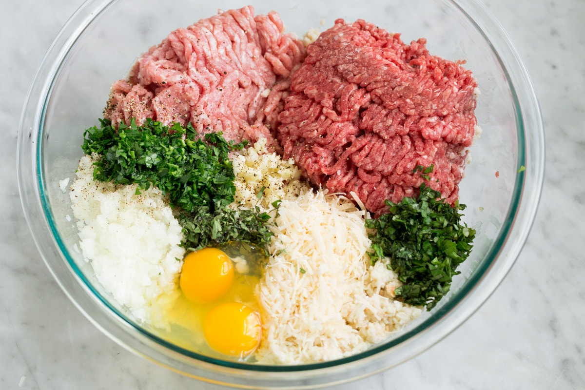 Ground beef, ground pork, fresh herbs, parmesan, eggs, onion, garlic and soaked breadcrumbs in a glass mixing bowl.