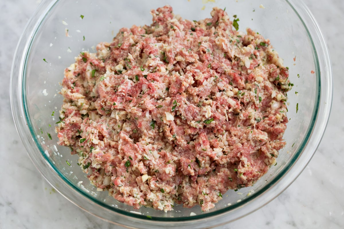 Mixed raw meatball mixture in a glass mixing bowl.