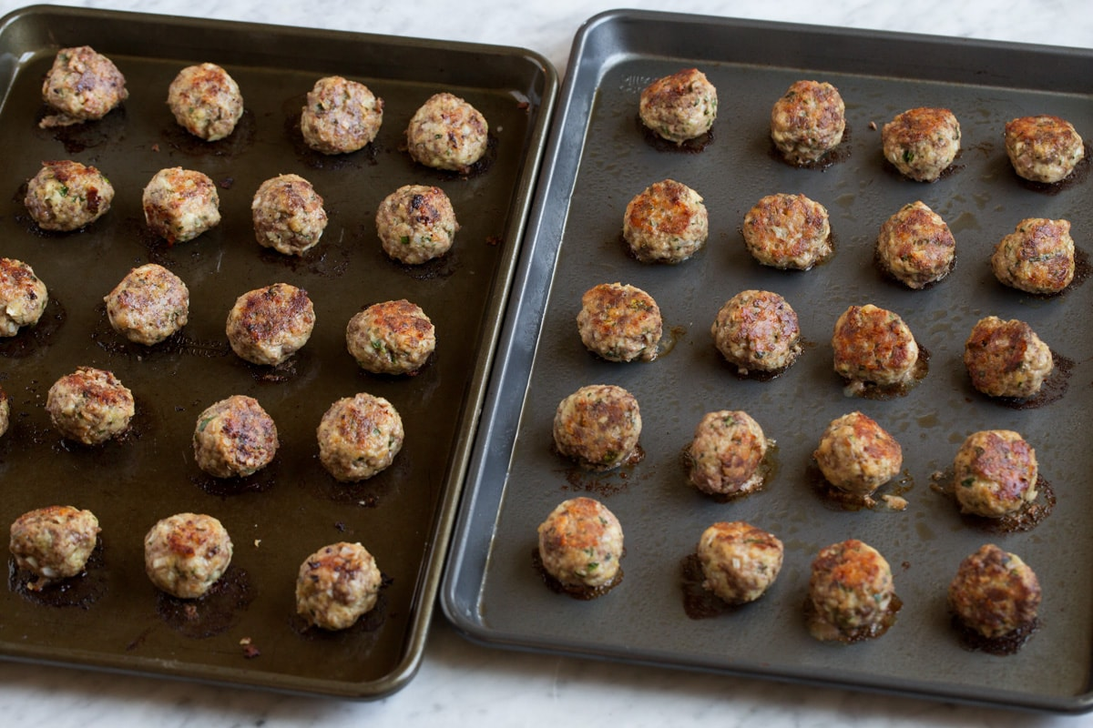 Cooked meatballs on two dark baking sheets.