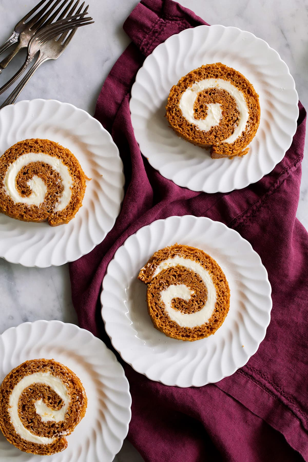 Four slices of pumpkin roll on a dessert plate.