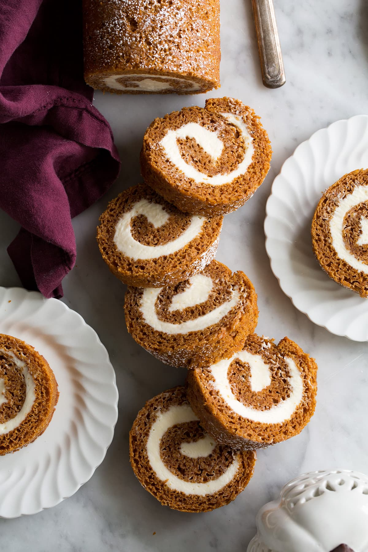 Sliced pumpkin roll on a marble surface.