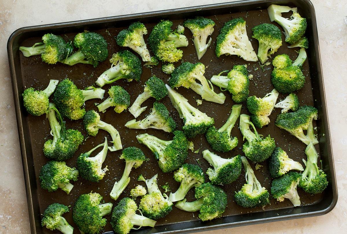 Raw boccoli florets on a baking sheet before baking.