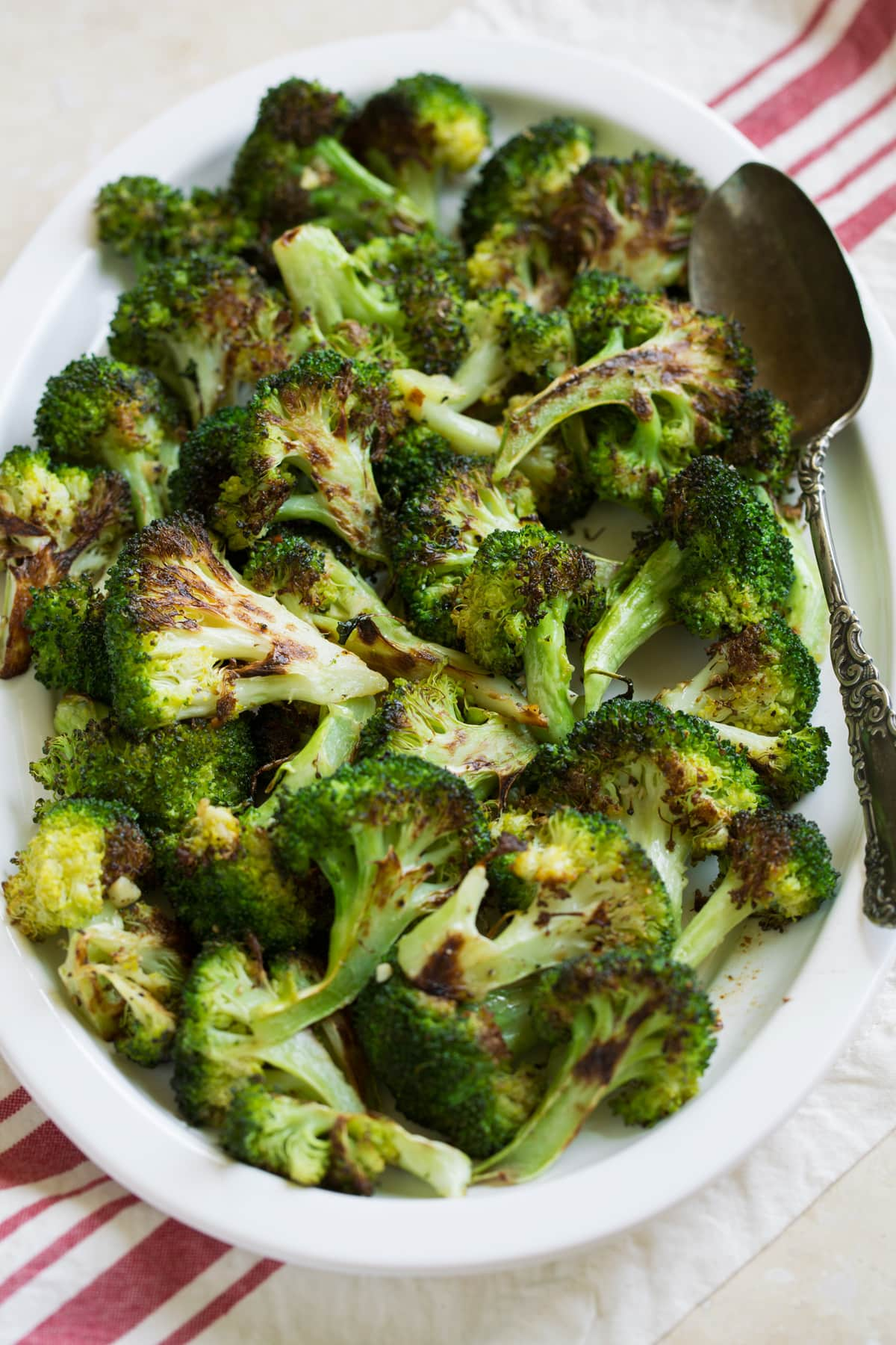 Broccoli on a serving plater over a striped napkin and beige table surface.