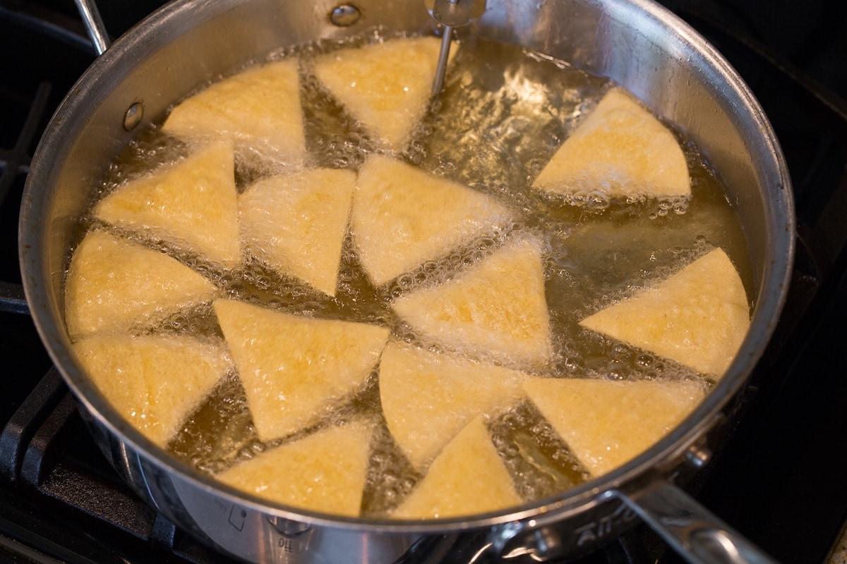 Frying tortilla chips in vegetable oil.