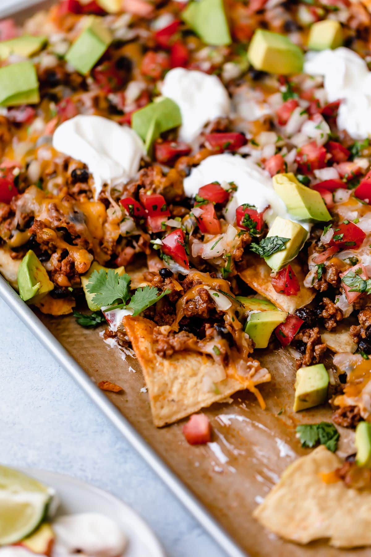 Nachos on a baking sheet with beef, black beans, cheese, pico, and sour cream.