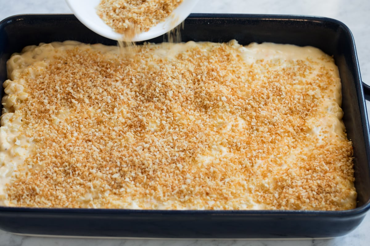 Pouring panko topping over macaroni and cheese in baking dish.