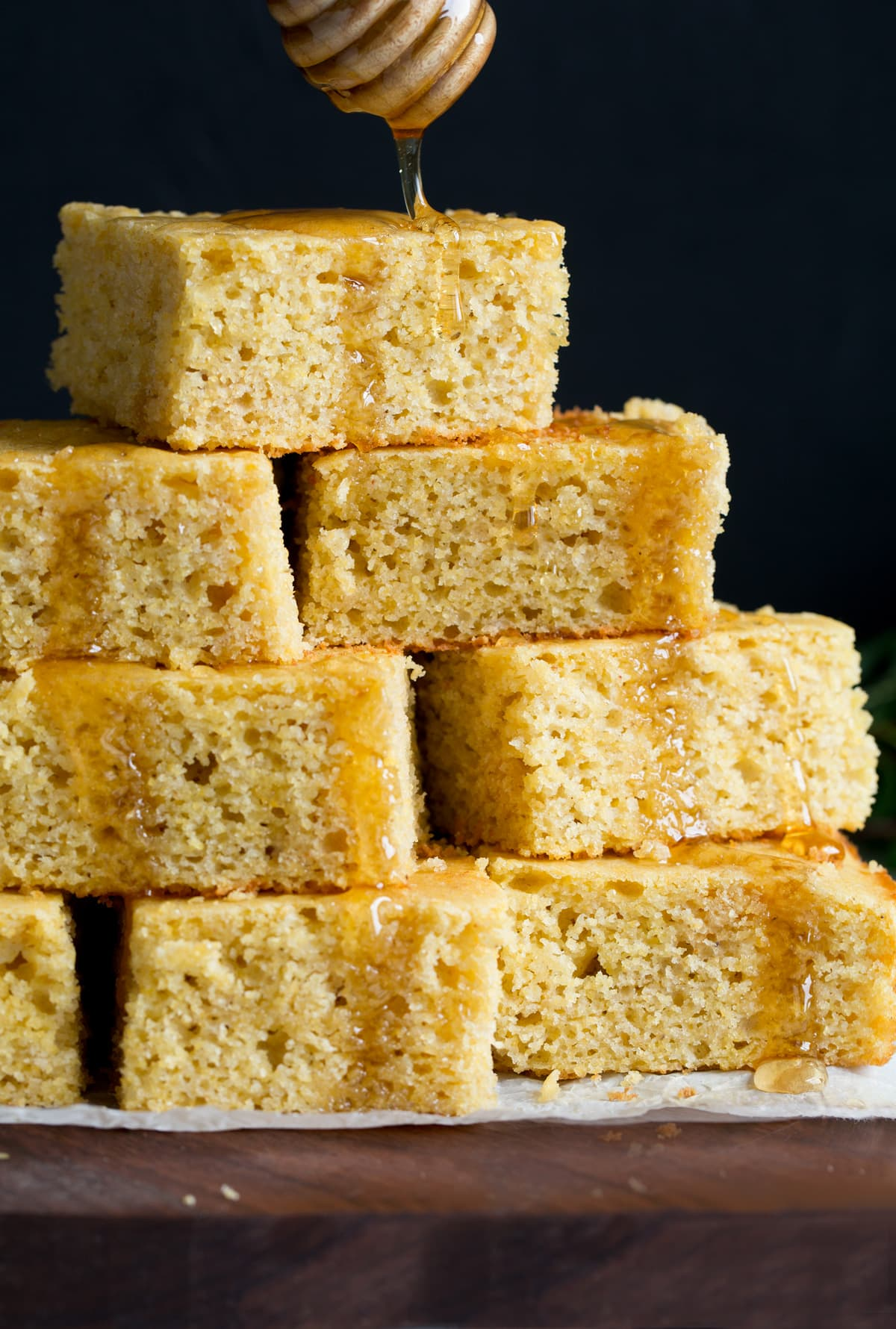 Drizzling honey on a pyramid of homemade cornbread