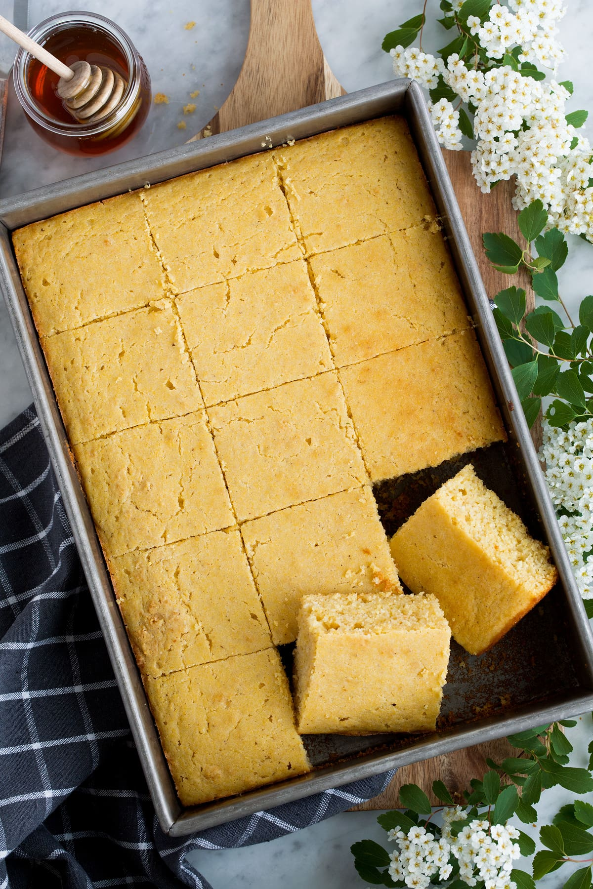 Overhead image of cornbread cut into squares in a baking dish.