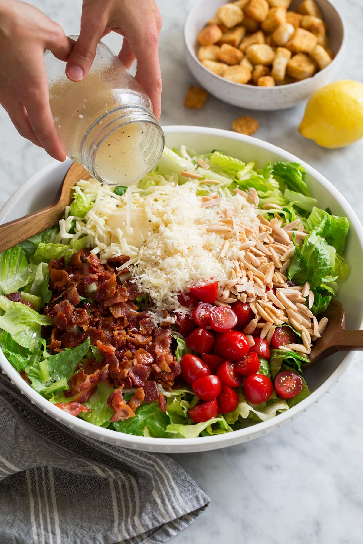 Pouring lemon dressing over salad in a large white bowl.