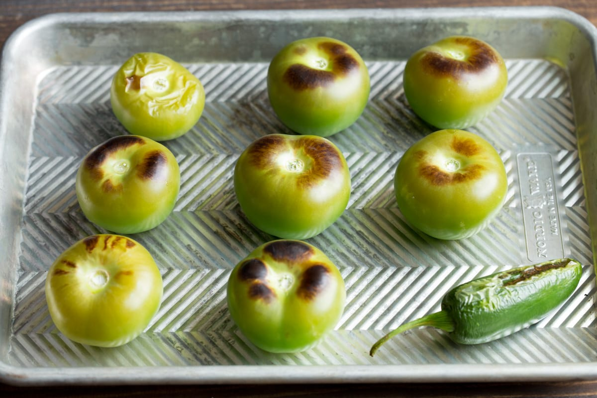 Roasted tomatillos and jalapeno on a baking sheet.