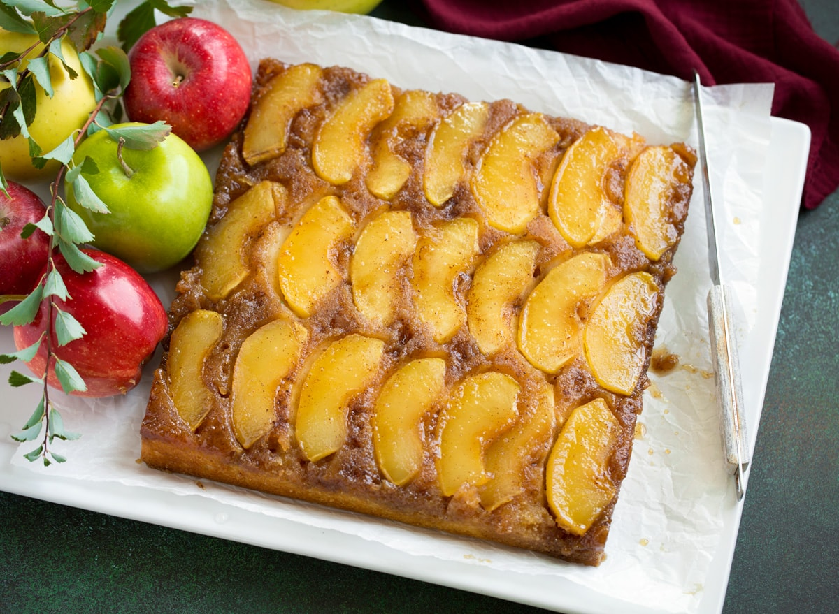 Whole apple upside down cake on a white serving plater.