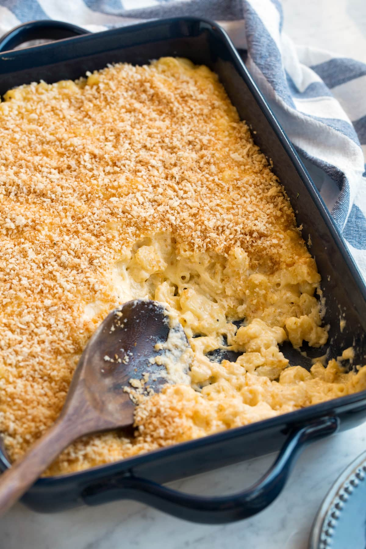 Baked macaroni in a casserole dish with a few scoops removed to show creamy cheesy macaroni noodles.