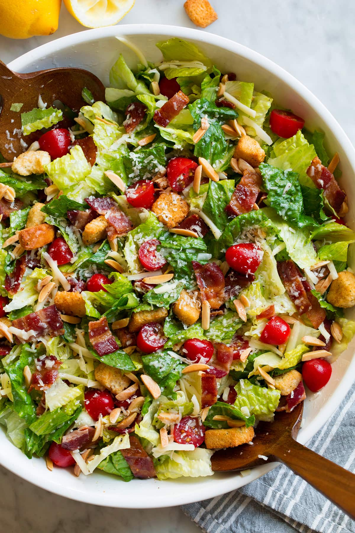 The Best Salad in a large salad bowl. Salad includes romaine lettuce, bacon, croutons, parmesan, swiss cheese, almonds, grape tomatoes and lemon vinaigrette dressing.