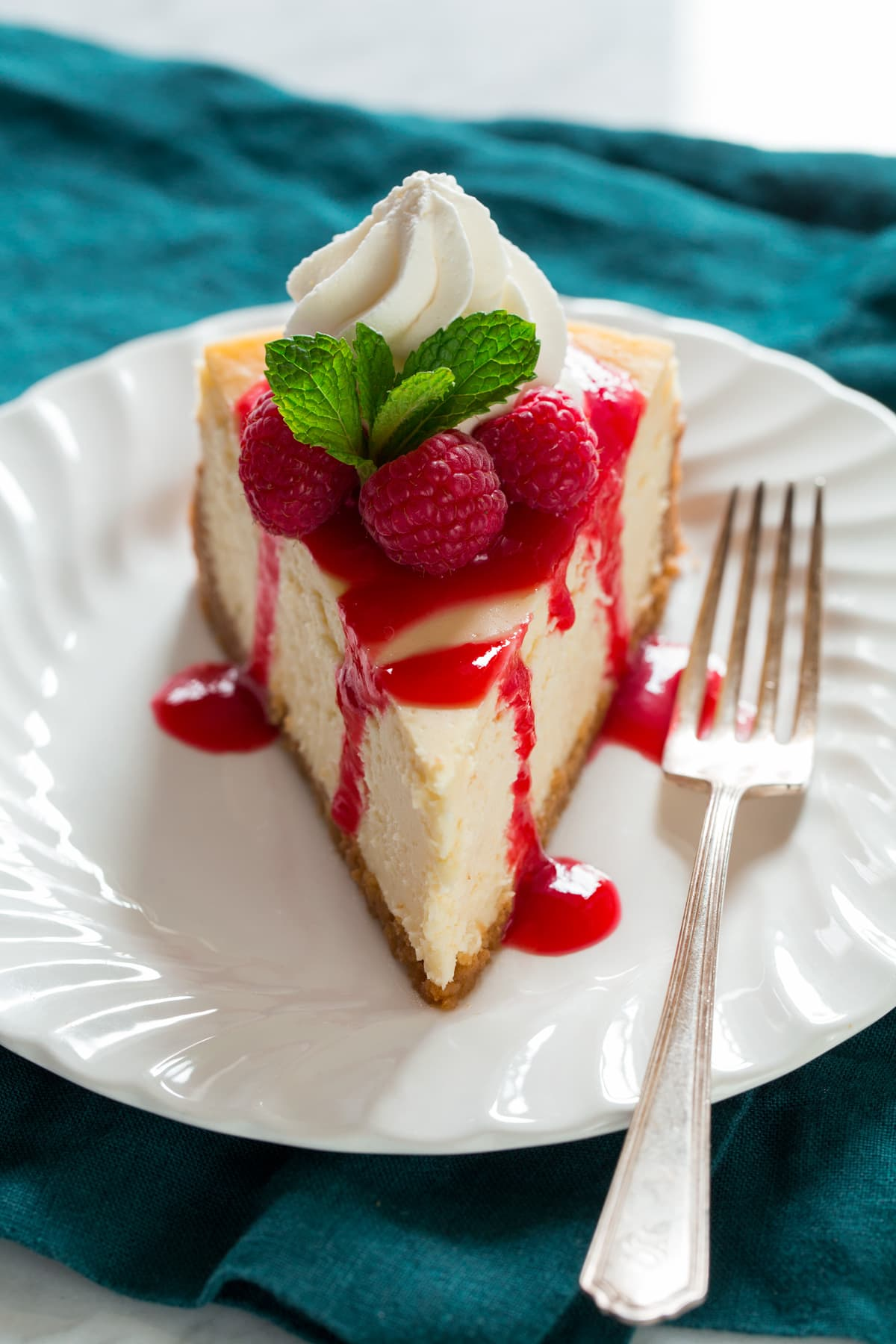 Slice of cheesecake topped with raspberry sauce, fresh raspberries, whipped cream and mint.