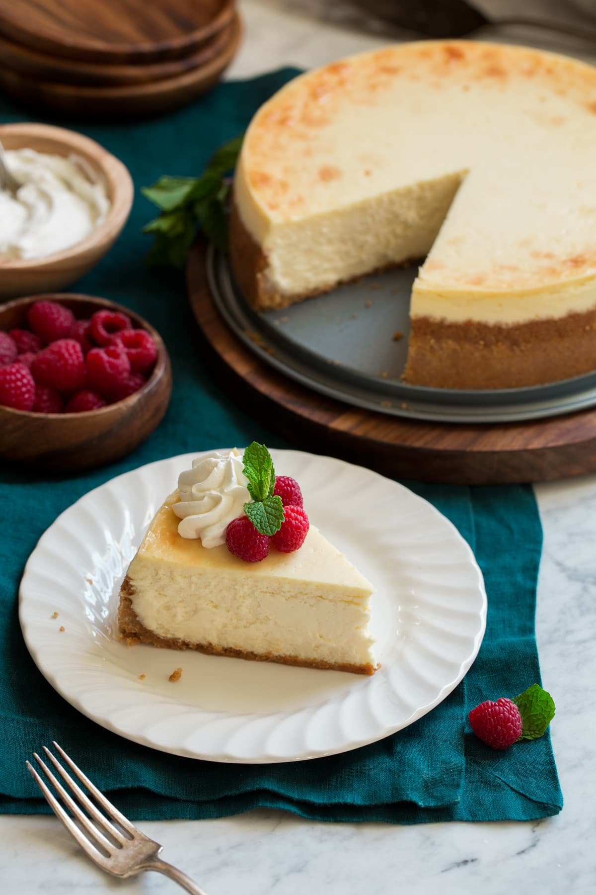 One slice of cheesecake with whole cheesecake in background.