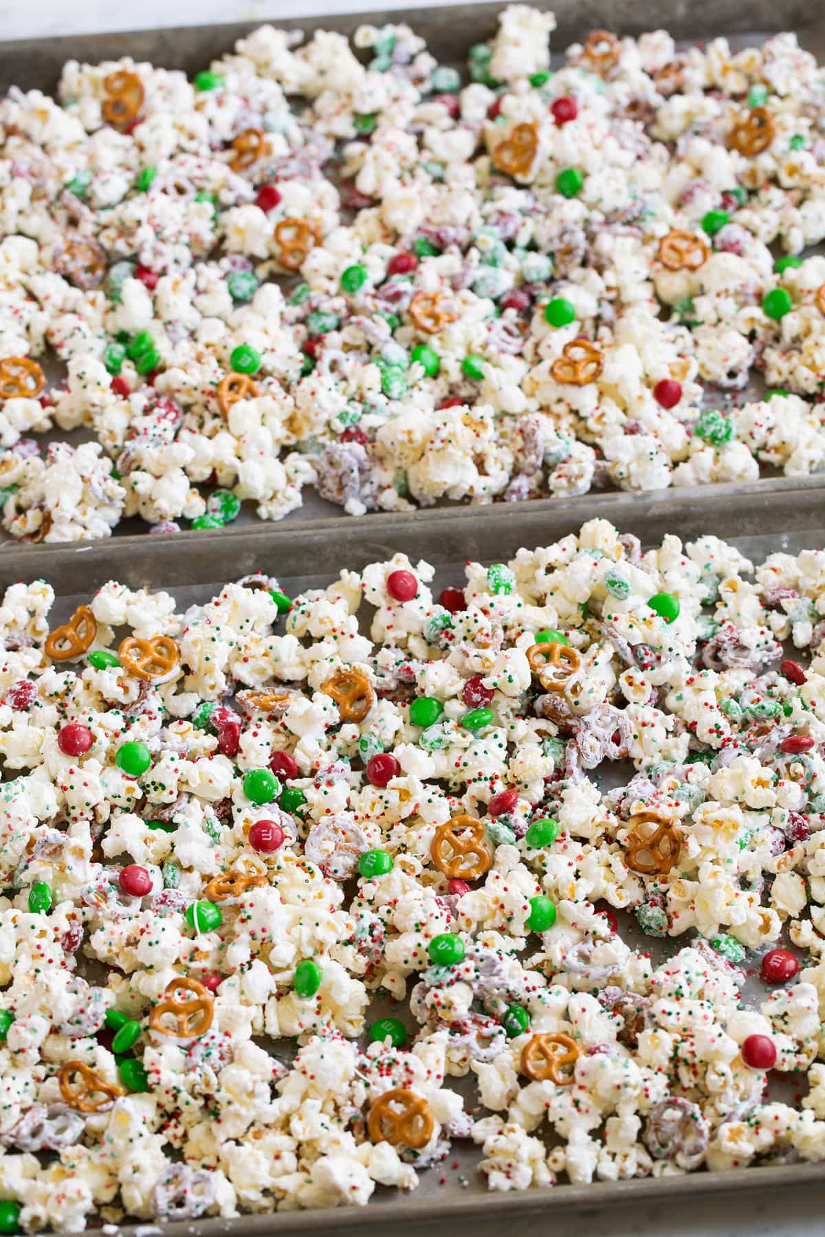 Christmas popcorn treat setting in baking sheets over parchment paper to dry.