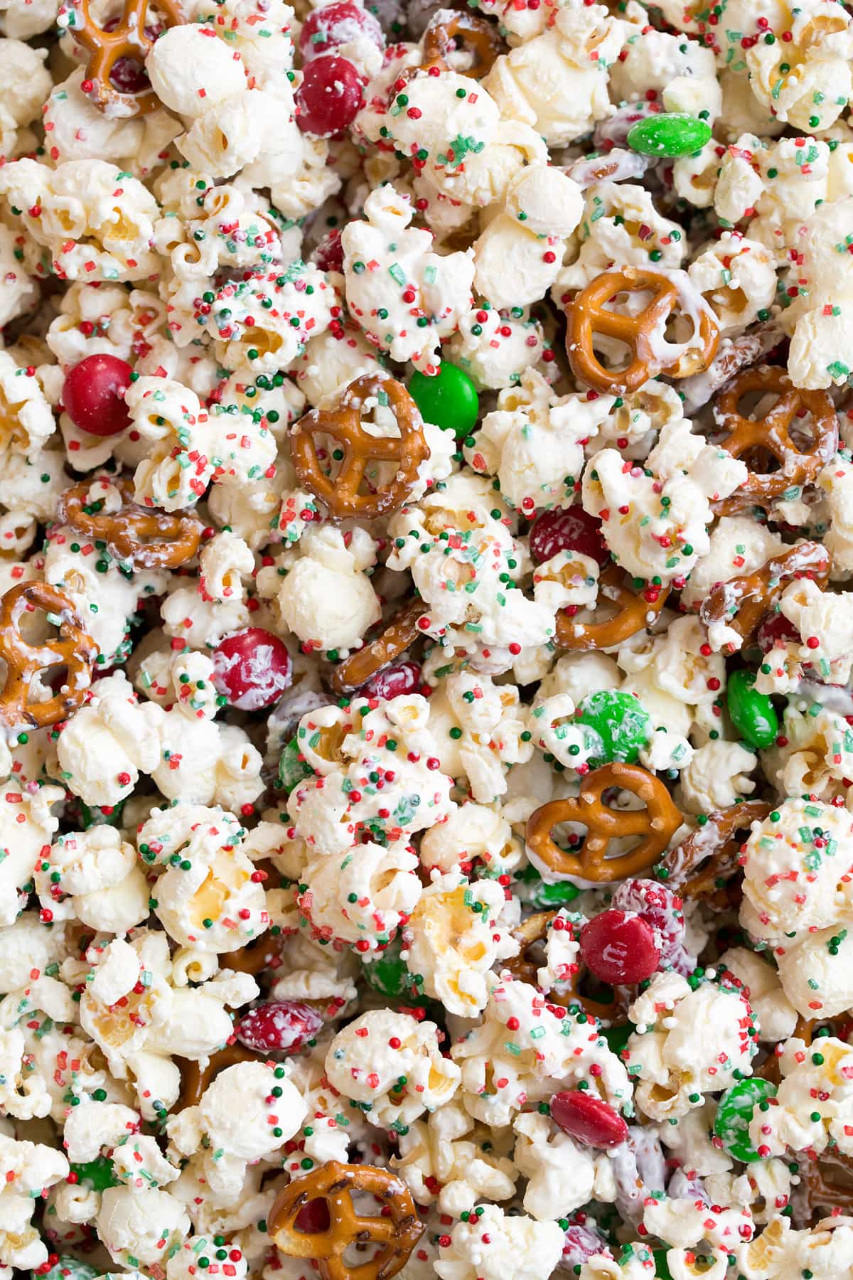 Close up image of white chocolate coated popcorn with pretzels sprinkles and m and m's.