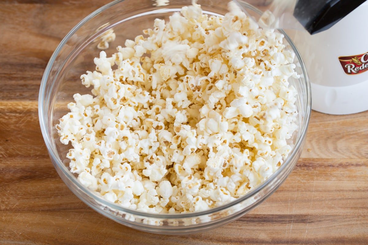 Popping popcorn into a glass bowl using an electric popcorn machine.