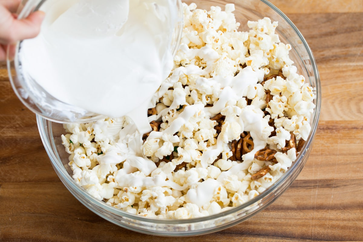 Pouring melted white chocolate candy coating over popcorn.