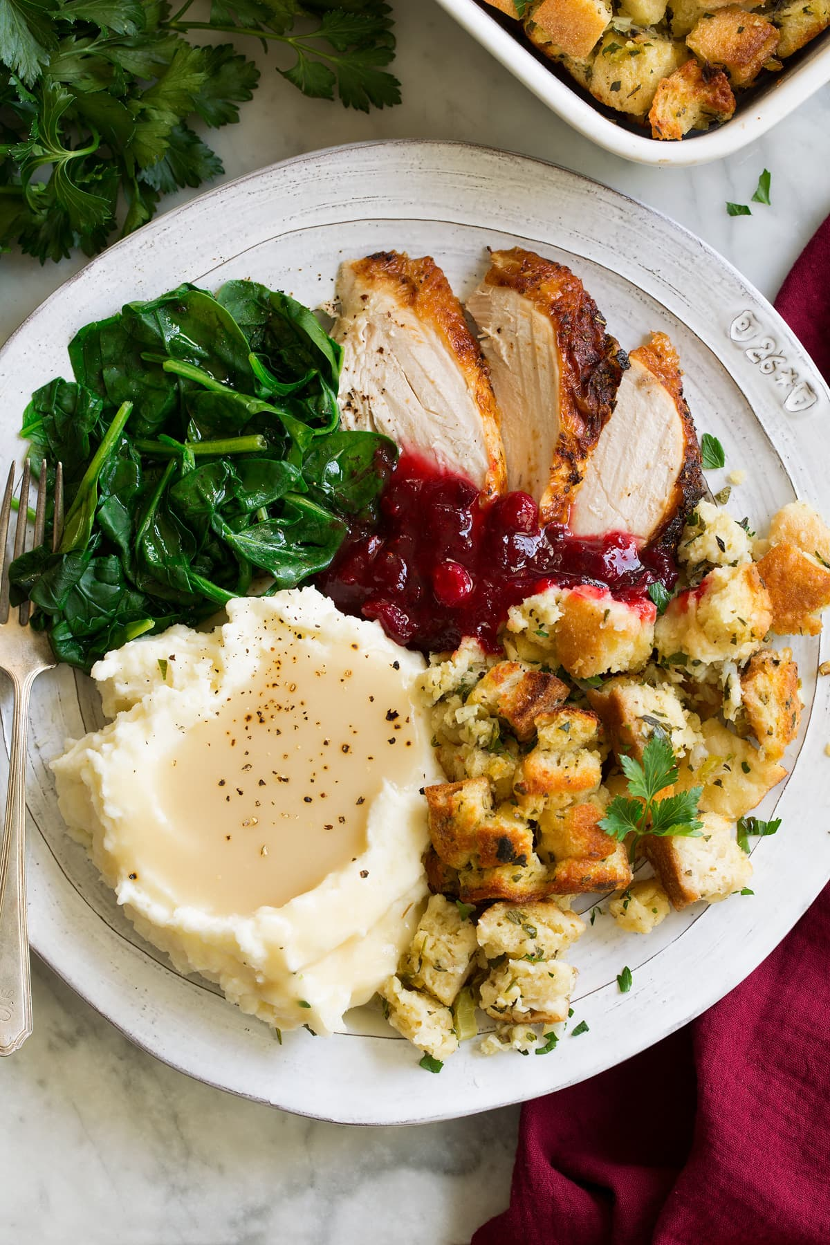 Stuffing on a large dinner plate with a side of mashed potatoes and gravy, turkey and steamed spinach.