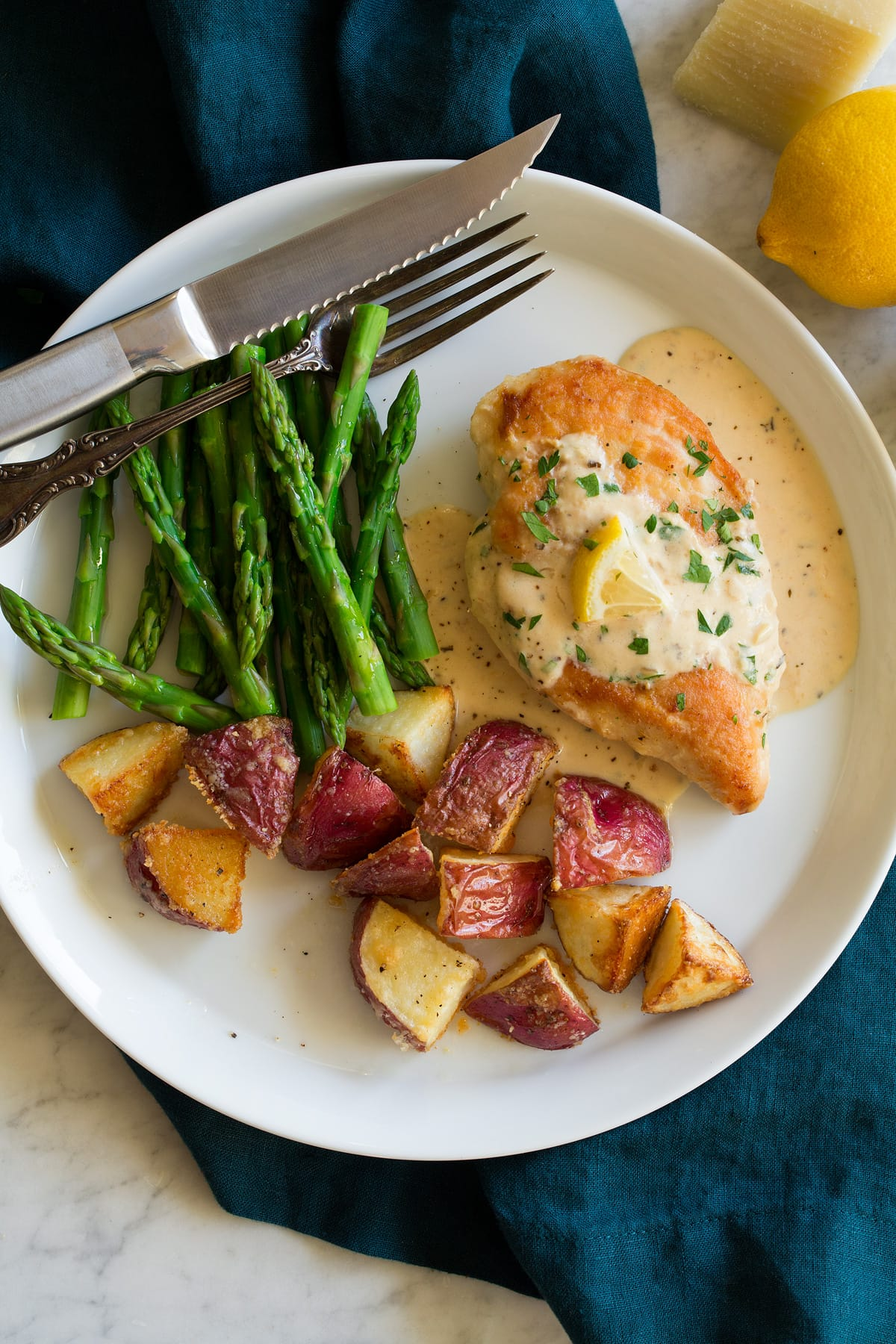 Plate with chicken breast topped with creamy lemon romano sauce and sides of potatoes and asparagus.