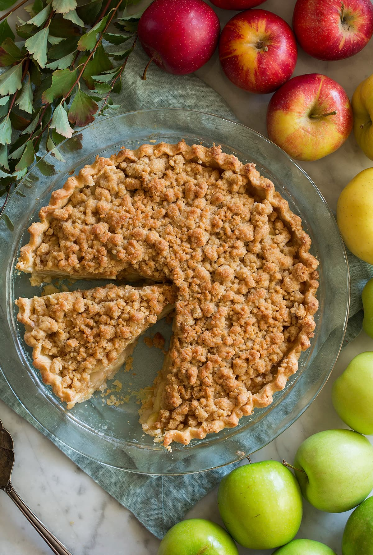 Overhead image of sliced Dutch apple pie with a colorful variety of apples around the pie.