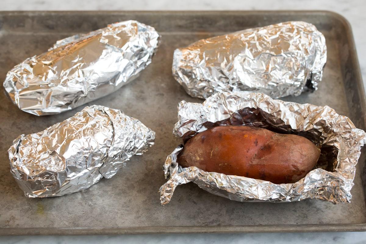 Bốn củ khoai lang bọc trong giấy nhôm, một mở, ngồi trên một tấm nướng.