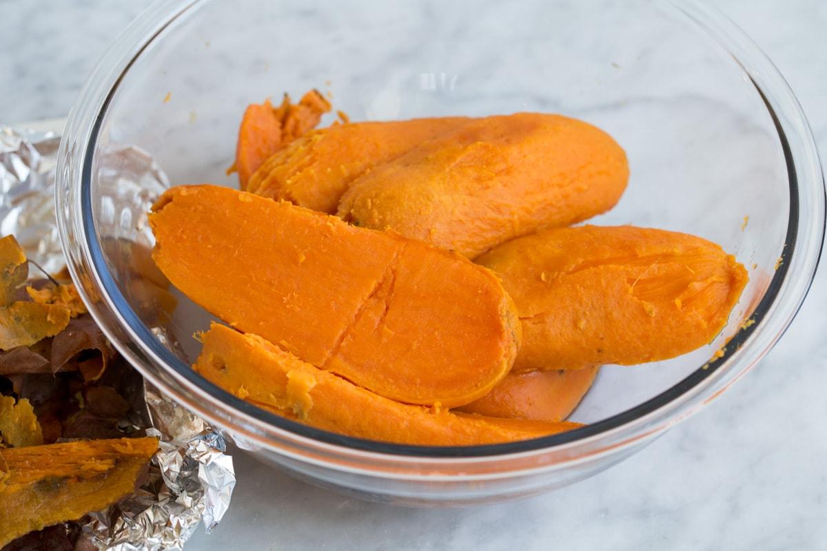 Nướng khoai lang không vỏ một nửa trong một bát trộn thủy tinh lớn. Chỉ ra cách làm khoai lang nghiền.
