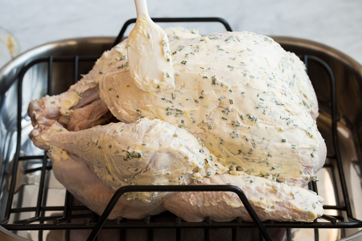 Showing how to prepare a turkey for roasting. Brushing herb butter on large turkey in a roasting pan using a spatula.