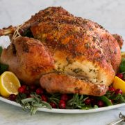Whole roasted turkey on a serving platter with herbs lemons and cranberries