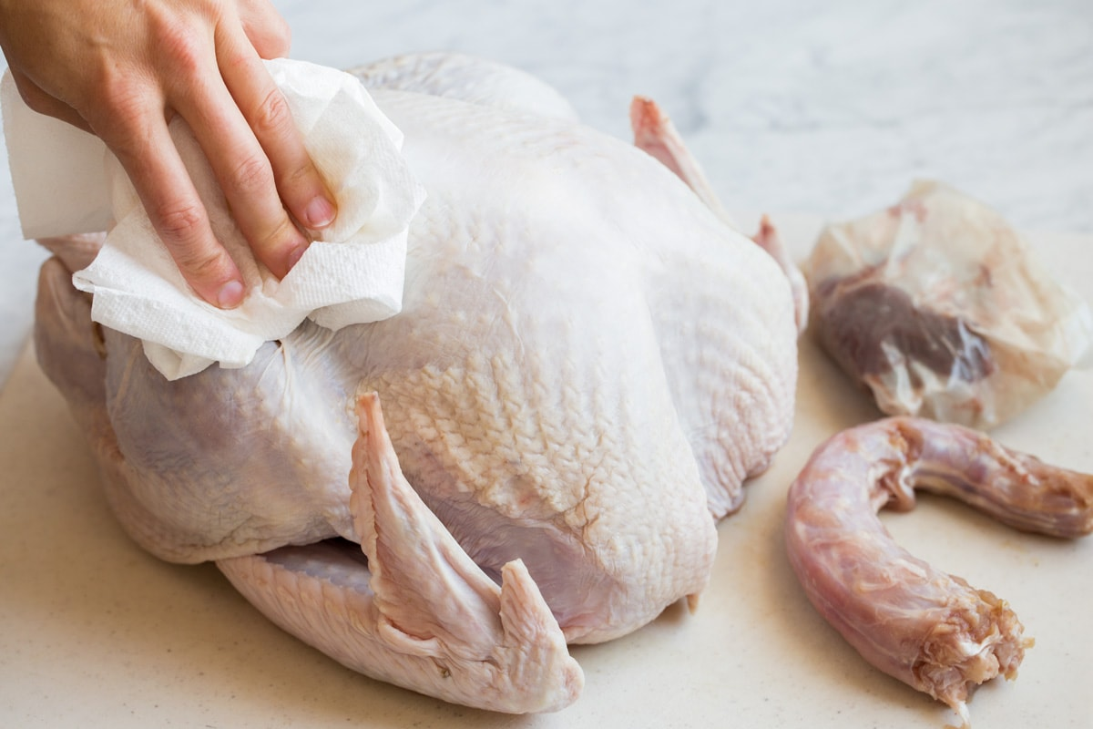 Drying turkey with paper towels so butter adheres better and skin browns better.