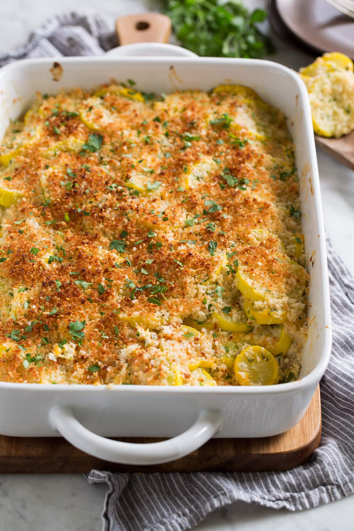 Baked yellow Squash Casserole in a white ceramic baking dish.