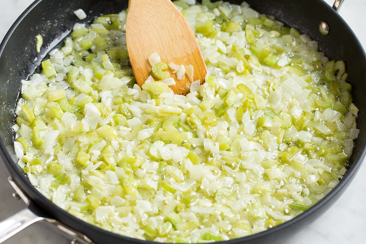 Sautéing celery, onions and garlic in a skillet with butter.