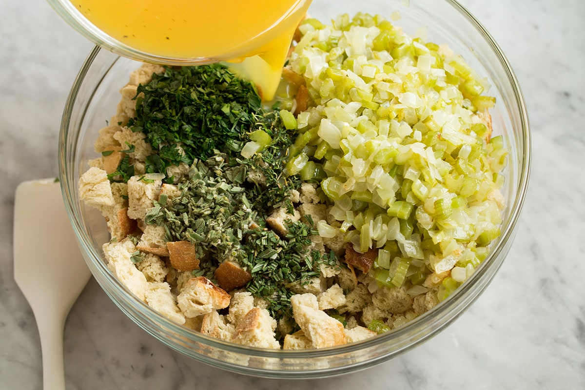 Showing how to make stuffing. Pouring broth mixture over dried bread cubes, celery mixture and herbs in a glass mixing bowl.