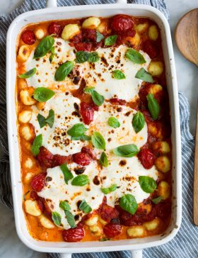 Baked Gnocchi in a white baking dish with marinara sauce, mozzarella and basil.