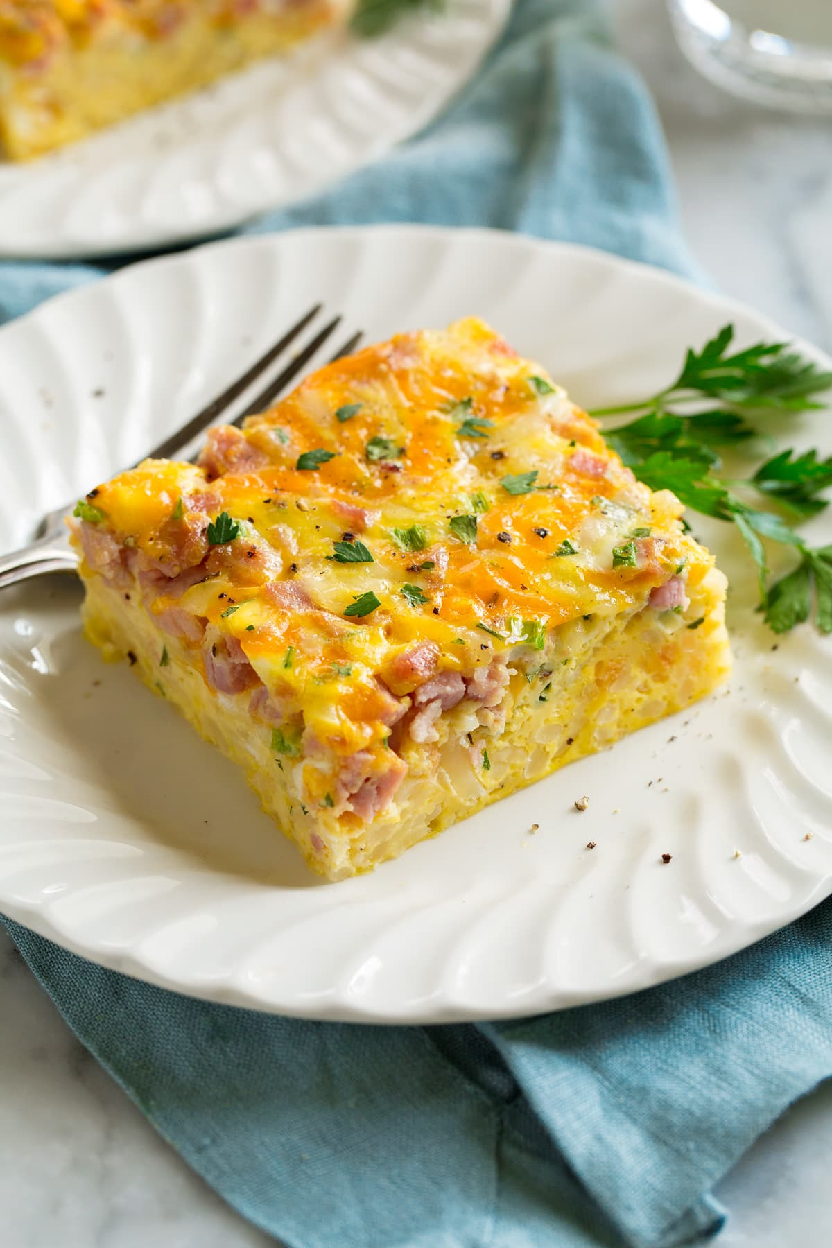 Slice of breakfast casserole filled with eggs, hash browns, ham and cheese on a white serving plate.