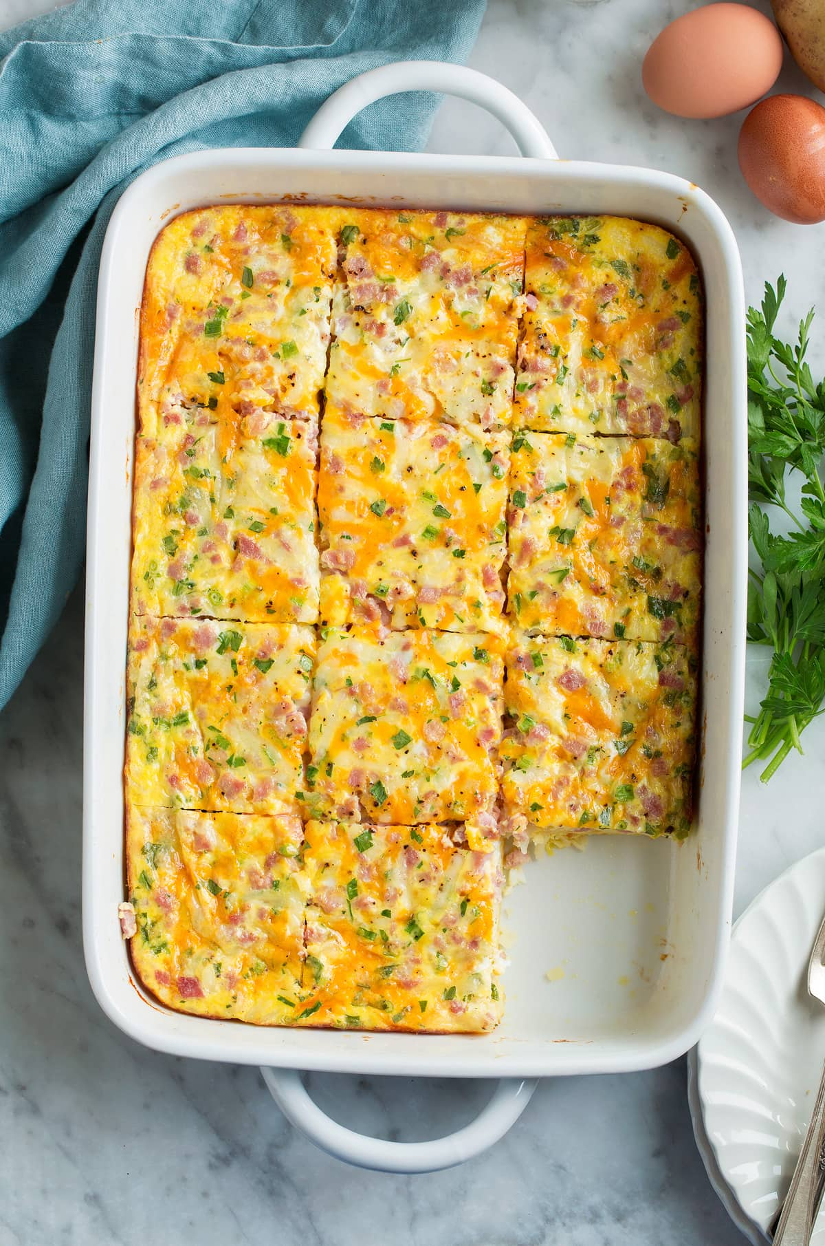 Overhead image of breakfast casserole in a baking dish cut into slices.