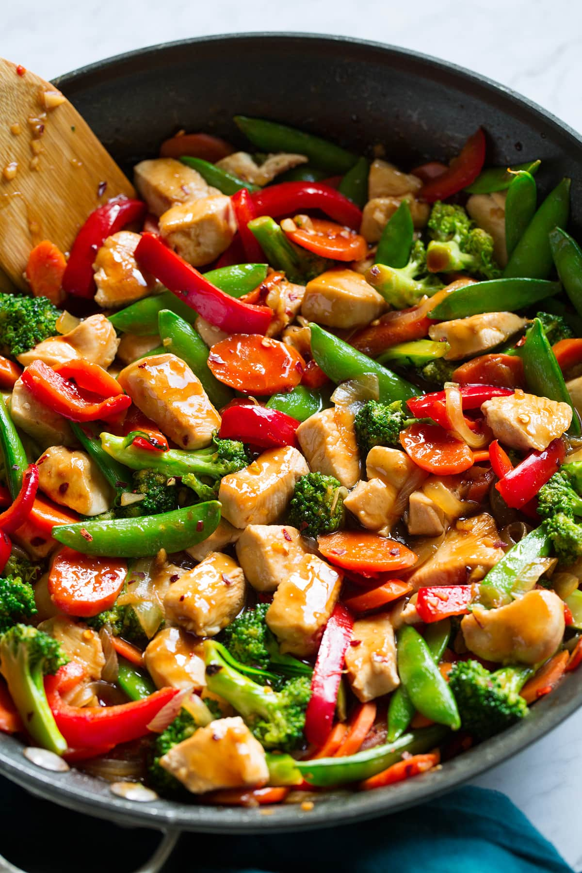 Close up image of chicken and vegetable stir fry in a skillet.