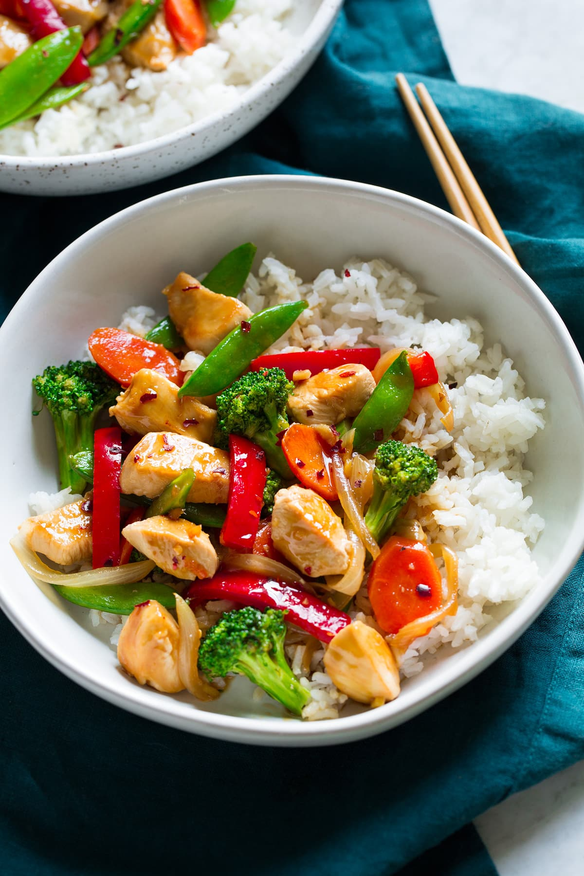 Chicken and vegetable stir fry on white rice in a bowl.