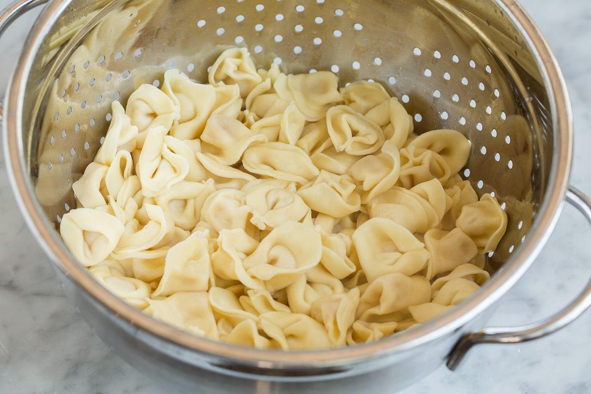 Tortellini draining in a colander.