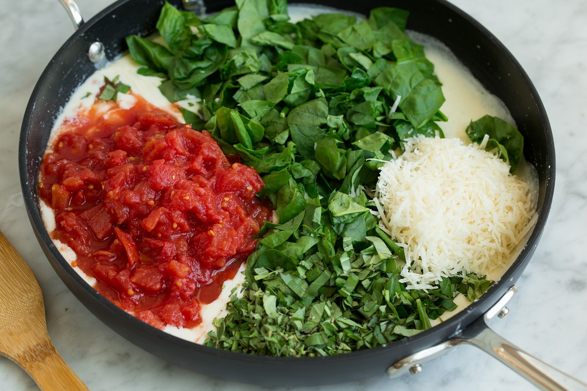 Spinach, tomatoes, fresh herbs and parmesan added to milk mixture in skillet.