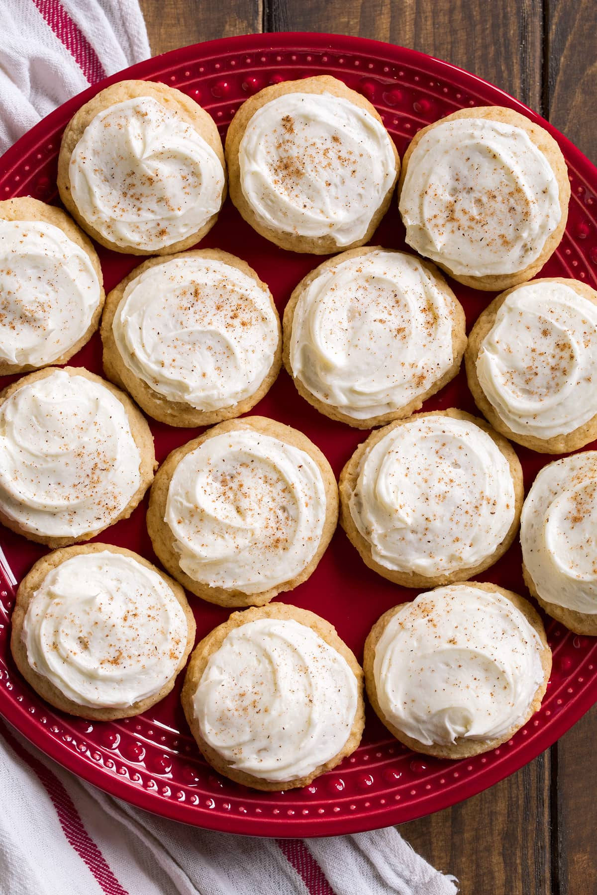 Red plate full of 14 frosted eggnog cookies.