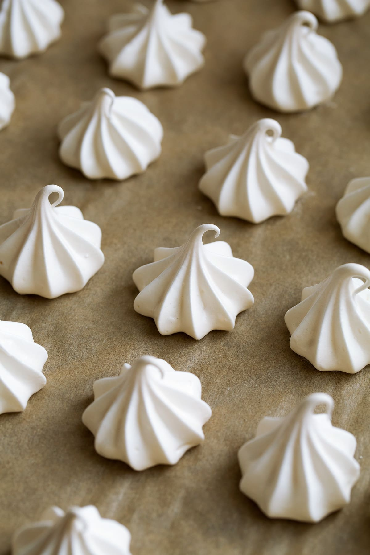 Meringue cookies on parchment paper on baking sheet shown after baking.